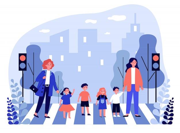 Zwei frauen überqueren straße mit gruppe von kindern