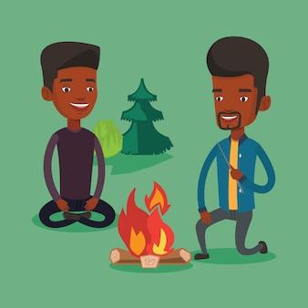 Zwei freunde sitzen am lagerfeuer auf dem campingplatz.