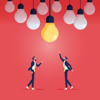 Zwei geschäftsleute stehen darunter und wählen glühbirne als symbol für geschäftliche kreativität