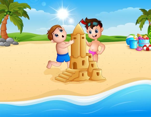 Zwei junge, der sandburg am strand bildet