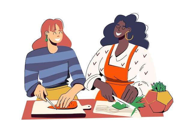 Zwei junge verschiedene schöne frauen schneiden gemüse kochen zusammen eine kulinarische meisterklasse