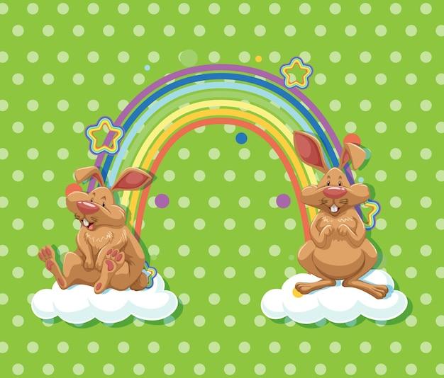 Zwei kaninchen auf der wolke mit regenbogen auf grünem tupfenhintergrund