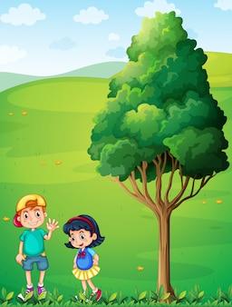 Zwei kinder auf dem hügel in der nähe des baumes