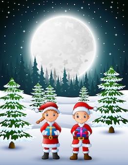 Zwei kinder in weihnachtsmann, der eine geschenkbox mit winterhintergrund nachts hält