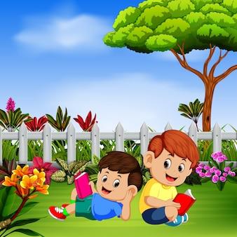 Zwei kinder lesen ein lesebuch im garten