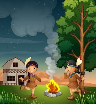Zwei kleine indianer mit lagerfeuer
