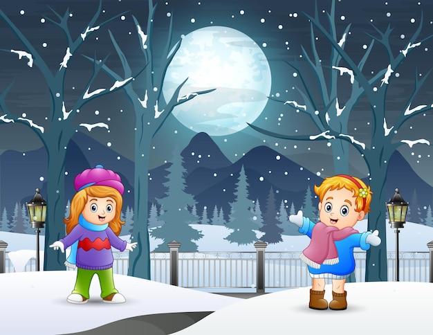 Zwei kleine mädchen, die draußen in der winternacht spielen