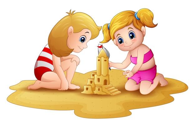 Zwei kleine mädchen, die sandburg am strand machen