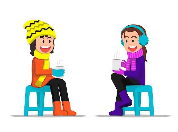 Zwei kleine mädchen, die sich unterhalten, während sie ein heißes getränk in der hand halten