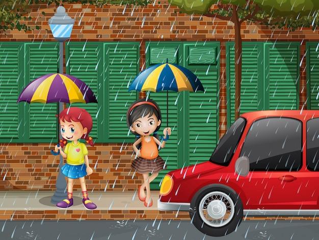 Zwei mädchen, die auf pflasterung im regen stehen
