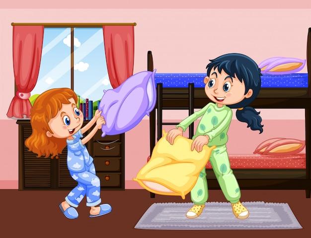 Zwei mädchen, die kissenschlacht im schlafzimmer spielen