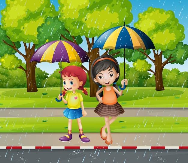 Zwei mädchen mit regenschirm im regen