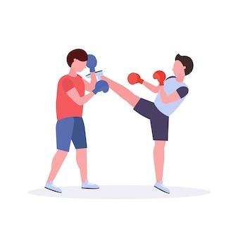 Zwei männer boxer, die thailändisches boxen in den roten handschuhenpaar-kämpfern üben, die am weißen hintergrund des gesunden clubkonzepts des kampfklubs üben