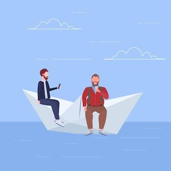 Zwei männer, die auf papierbootjungen schwimmen, die geräte verwenden, die zusammen digitales sucht-web-surfkonzept in voller länge flach reisen