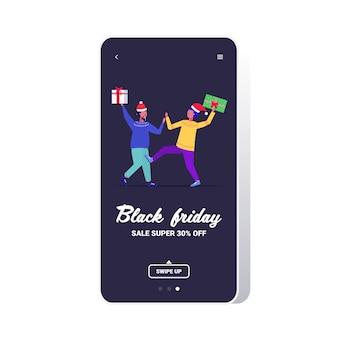 Zwei männer käufer in santa hüte kämpfen für die letzten geschenkboxen kunden auf saisonalen shopping sale kampfkonzept smartphone bildschirm online mobile app in voller länge