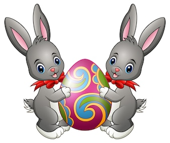 Zwei nette Kaninchen, die Osterei auf einem weißen Hintergrund halten