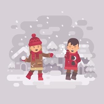 Zwei nette kinder, die schneebälle in einem winterdorf spielen