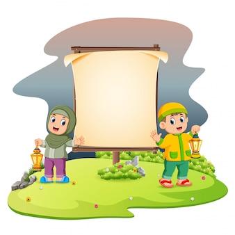 Zwei nette kinder mit der ramadan-laterne stehen neben dem leeren rahmen im garten