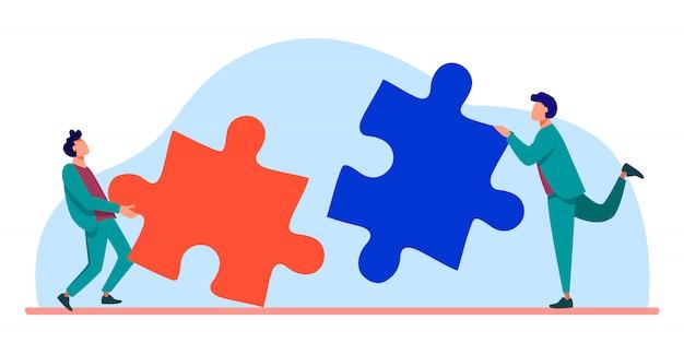 Zwei personen verbinden puzzleteile