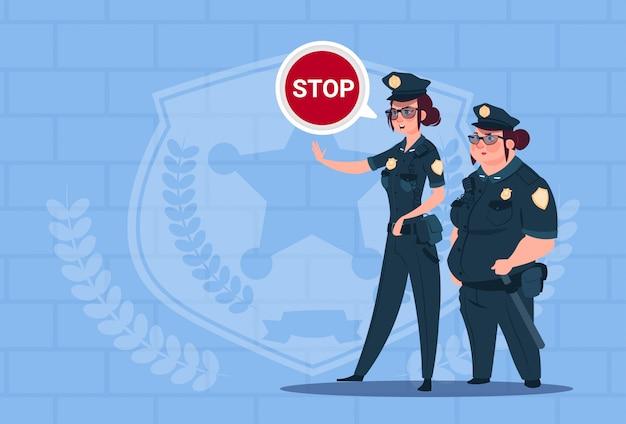 Zwei polizeifrauen, die stoppschild tragen, das einheitliche weibliche schutz auf blauem ziegelstein-hintergrund trägt