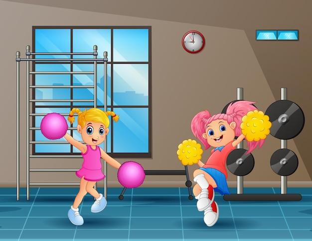 Zwei süße mädchen üben cheerleading im fitnessstudio