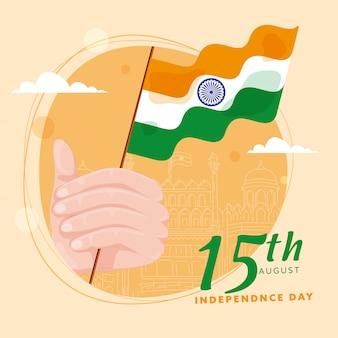 15 de agosto dia da independência design de cartaz com a mão segurando a bandeira indiana e linha arte red fort monument em fundo laranja pastel.