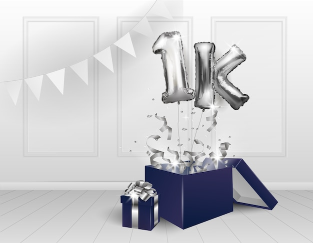1k mil assinantes. balões prateados. a celebração do aniversário. balões com confetes cintilantes saem voando da caixa, número 1.