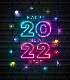2022 luz de néon número feliz ano novo e lâmpada colorida à noite com design na parede de blocos