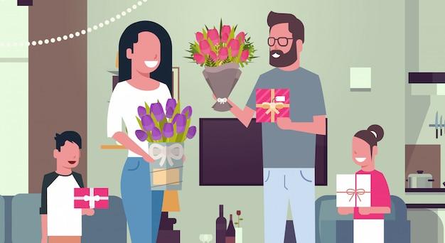 8 de março de férias família feliz parabenizando a mãe com o dia de mulheres dando presentes e flores em casa