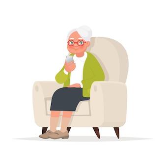 A avó se senta em uma cadeira e segura um telefone na mão.