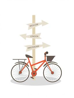 A bicicleta está estacionada no poste com sinais de direção.