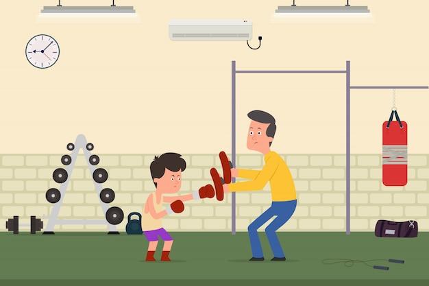 A criança está sendo treinada para boxe com o treinador na academia
