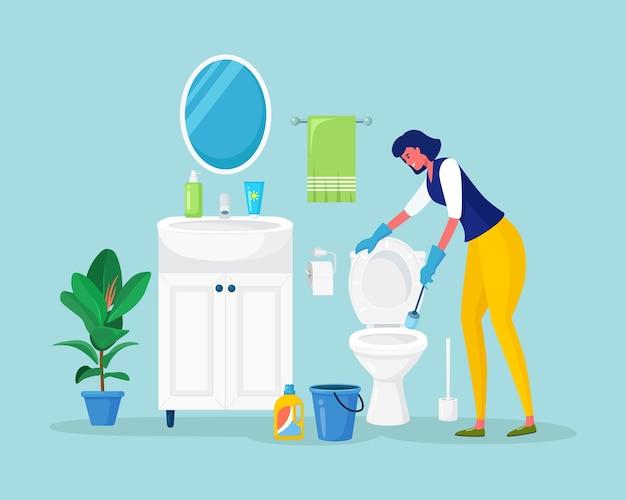 A dona de casa lava o vaso sanitário com detergente em um balde