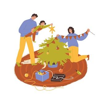 A família está decorando a árvore de natal. o pai segura a filha nos braços