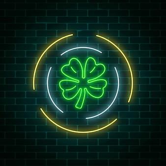 A folha de trevo brilhante de néon assina dentro quadros do círculo em um fundo escuro da parede de tijolo. trevo verde