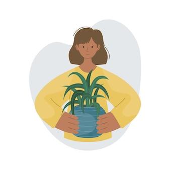 A garota com a planta da casa em uma panela nas mãos dela. plantar plantas. plantas decorativas no interior da casa. estilo simples.