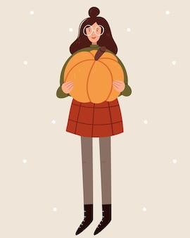 A garota com roupas de outono segurando uma grande abóbora.