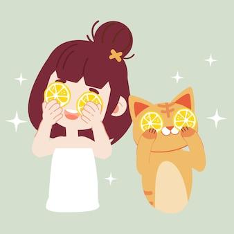 A garota mascarando o rosto com limão com gato bonito.