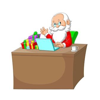 A ilustração do papai noel sentado em sua mesa com o laptop e o presente em sua mesa
