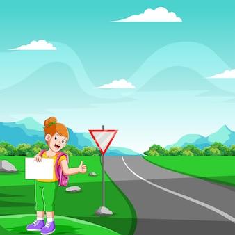 A jovem está de pé e segurando a lousa em branco para parar o carro