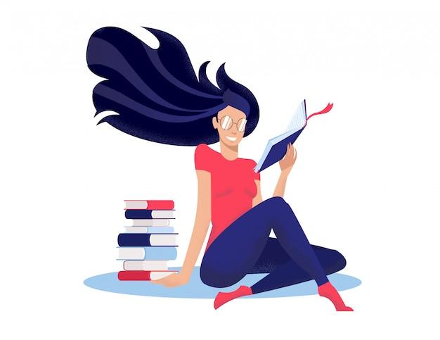 A jovem mulher lê o livro, sentando-se no assoalho de pernas cruzadas nwet à pilha de livros.