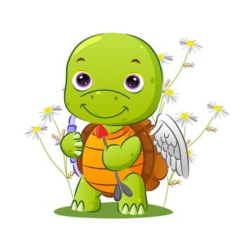 A linda tartaruga cupido está segurando uma flecha para espalhar o amor e está parada no jardim da ilustração
