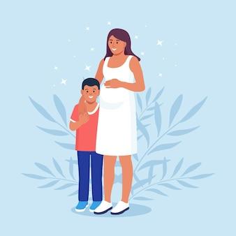 A mãe grávida abraça o filho. esperando o nascimento da criança. gravidez. mulher e menino se abraçam. família feliz