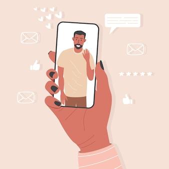 A mão de uma mulher segura um telefone com um homem na tela. um aplicativo para namoro e videochamadas.