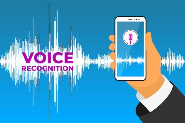 A mão do assistente pessoal e do aplicativo móvel de reconhecimento de voz segura o smartphone com o botão do microfone ligado