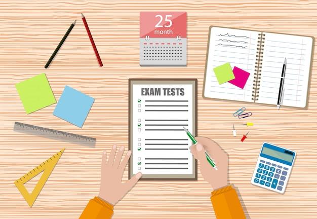 A mão do estudante preenche papel de teste de exame