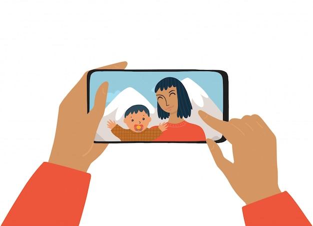 A mão feminina segura um smartphone. o conceito de fotografia, bate-papo, chamada de vídeo. mulher e criança sorri e tira uma selfie. a mãe e o filho tiram uma foto nas férias.