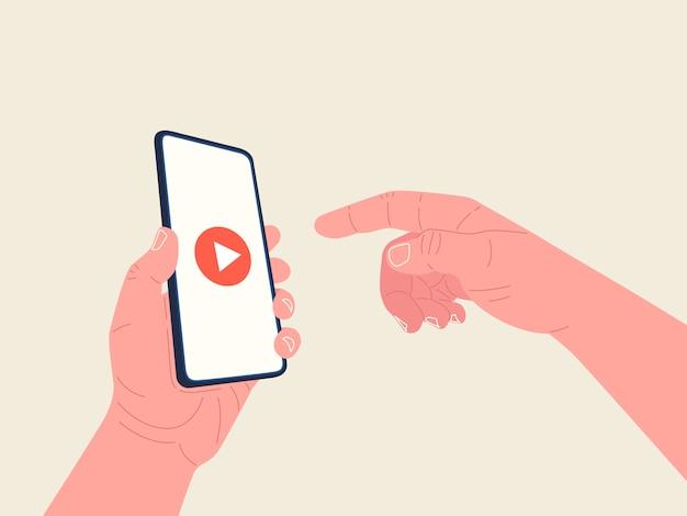 A mão segurando o smartphone e a outra mão alcança a tela para iniciar o vídeo. player de vídeo na tela