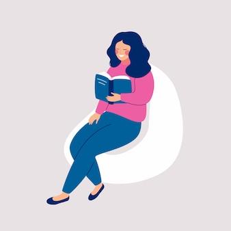 A menina de sorriso com livro senta-se na cadeira do beanbag.