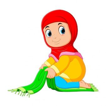 A menina deligente está dobrando seu tapete de oração verde
